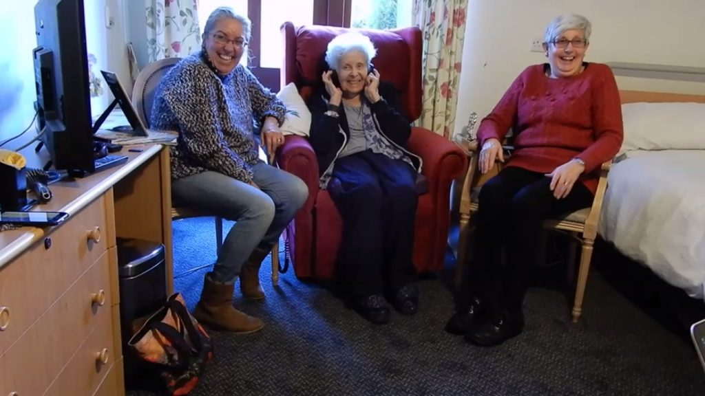 A care home resident enjoying her favourite music with her family.